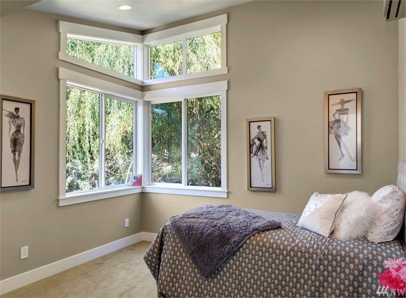 This bedroom has white framed windows and beige walls adorned with slim framed artworks.