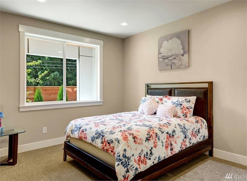 Another bedroom with a glass top table and a wooden bed placed under the floral artwork.