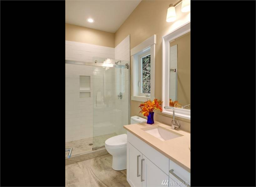 This bathroom has a walk-in shower, a toilet, and a sink vanity paired with a white framed mirror.