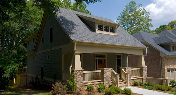 Angled side view showing the gray exterior siding, stone columns, and a gable dormer.