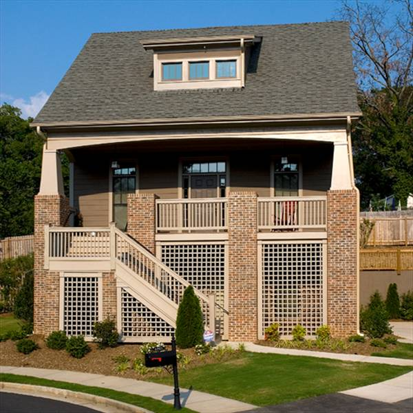 The home's rear view showcases the large sun deck and two-car garage framed with red brick columns.