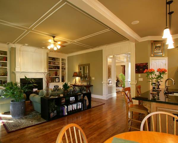 Family room with a coffered ceiling and a fireplace flanked by built-in shelves.