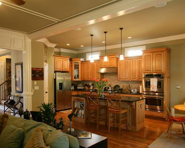 The kitchen is equipped with stainless steel appliances, wooden cabinetry, and a granite top island lit by warm glass pendants.