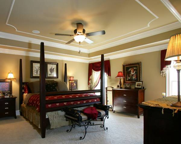 Primary bedroom furnished with wooden dressers and a four-poster bed complemented with an intricate metal bench.