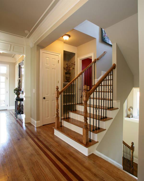 The foyer features a traditional staircase with wooden treads and ornate wrought iron spindles.
