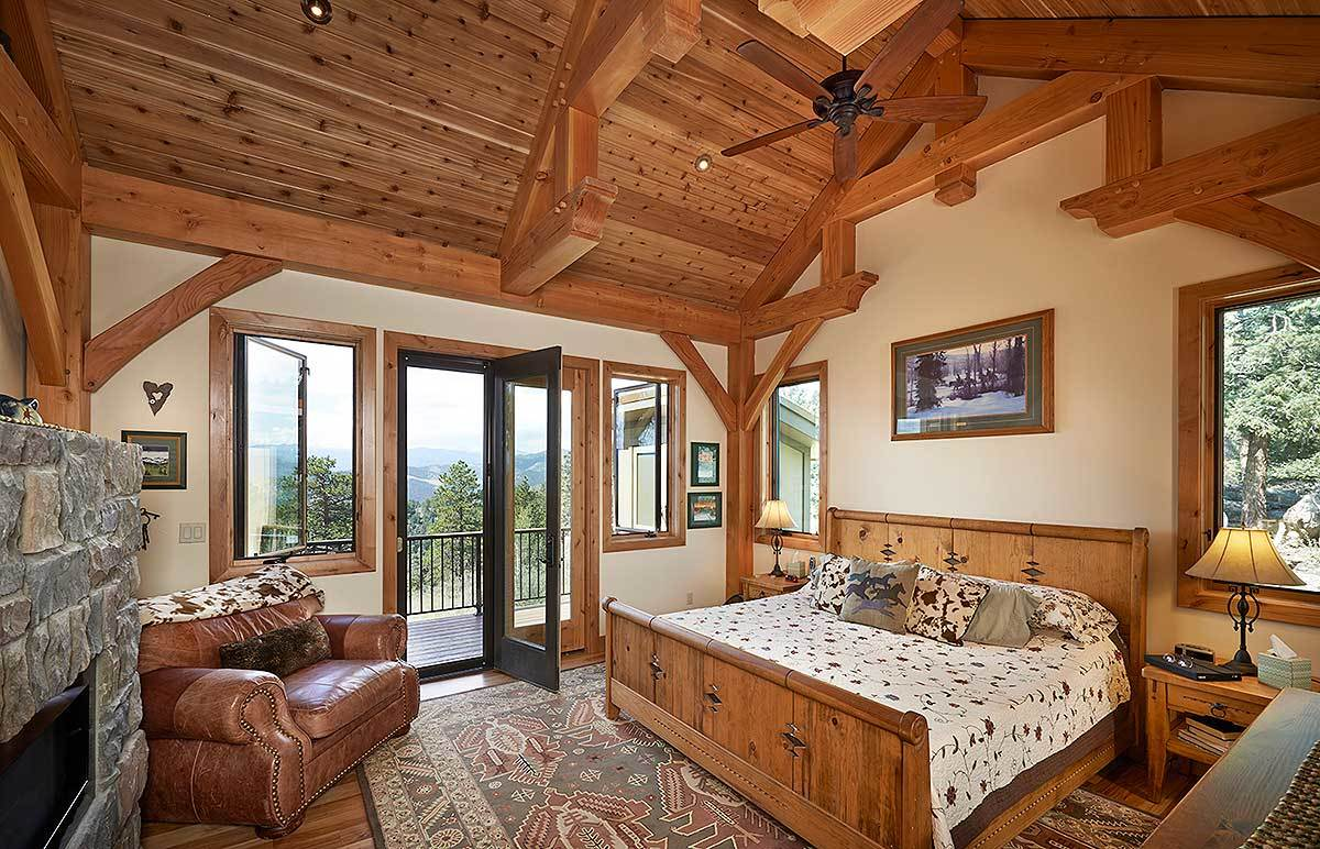 The primary bedroom has a vaulted ceiling, stone fireplace, wooden furnishings, a leather armchair, and a glass door that opens out to the wide deck.