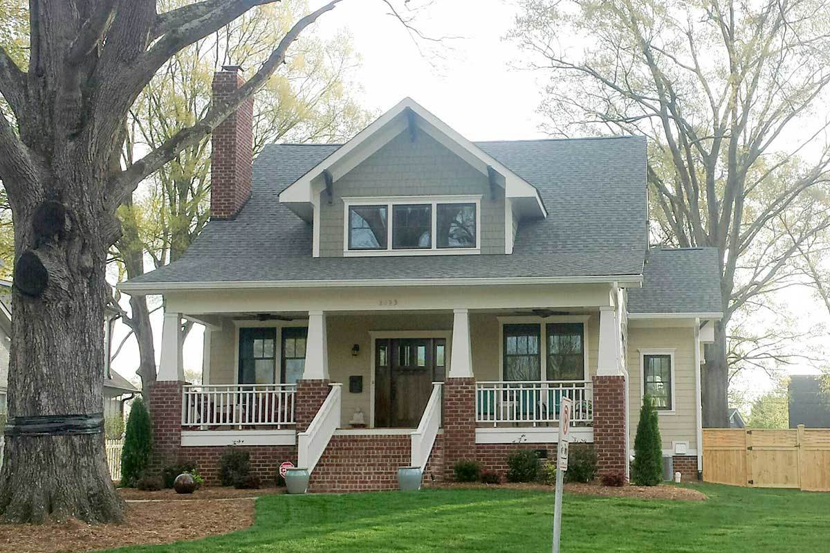 Home's front view showing the large front porch and a center dormer window that sits on the gable roof.