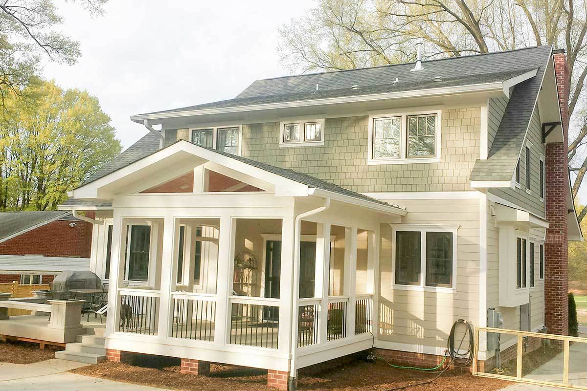 Rear exterior view showing the screened porch framed with white wooden trims and wrought iron railings.