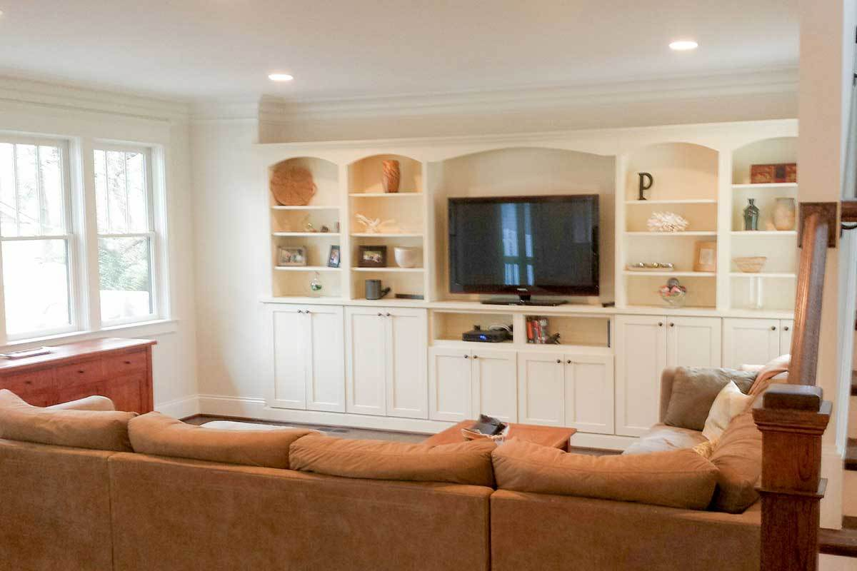 The living room offers a brown sectional sofa and a flatscreen TV flanked with built-in cabinets.