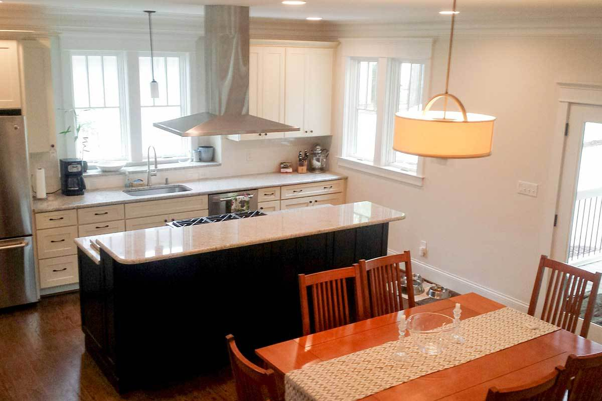 Eat-in kitchen with stainless steel appliances, white cabinets, and a two-tier island fitted with a cooktop.