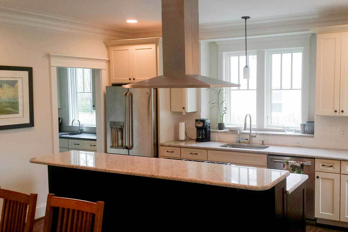 Natural light flows in through the white-framed windows of the kitchen.