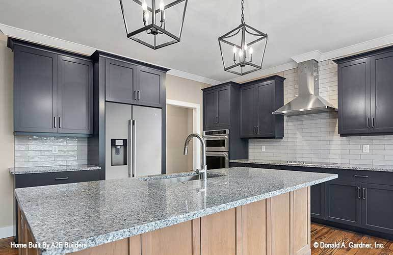 The kitchen is equipped with custom gray cabinets, granite countertops, subway tile backsplash, and a large center island.