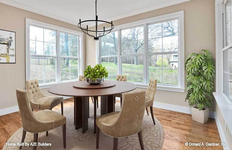 Bright dining area with beige tufted chairs and a round dining table illuminated by a wrought iron chandelier.