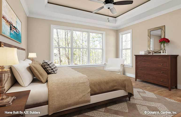 The primary bedroom has a striking tray ceiling and a natural hardwood flooring topped with a patterned area rug.