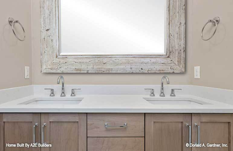 A large rustic mirror hangs above the wooden vanity with dual sink and a quartz countertop.