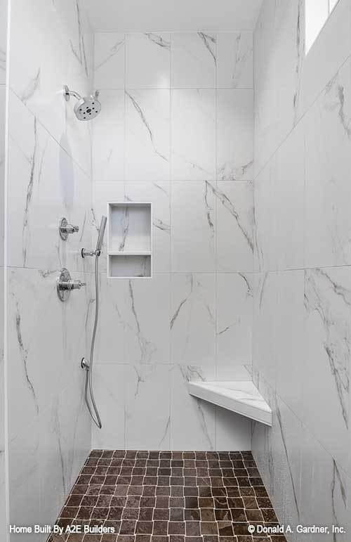 Walk-in shower with white marble tiled walls, inset shelves, a corner seat, and chrome fixtures.