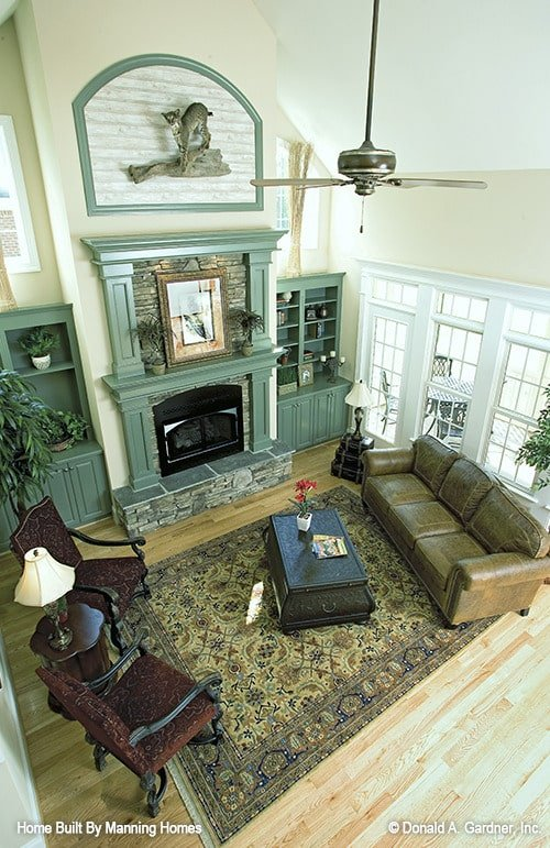 View of the living room from the second-floor balcony showing its high cathedral ceiling and a light hardwood flooring topped with a classic area rug.