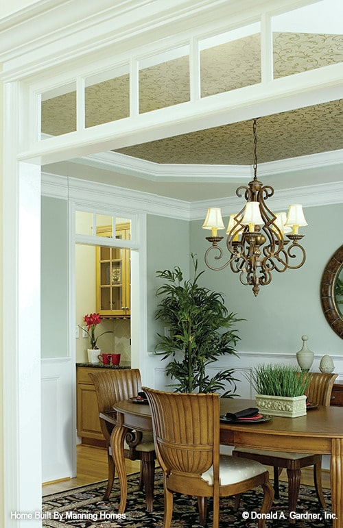 An ornate chandelier illuminates the formal dining room offering an oval dining table and cushioned chairs.