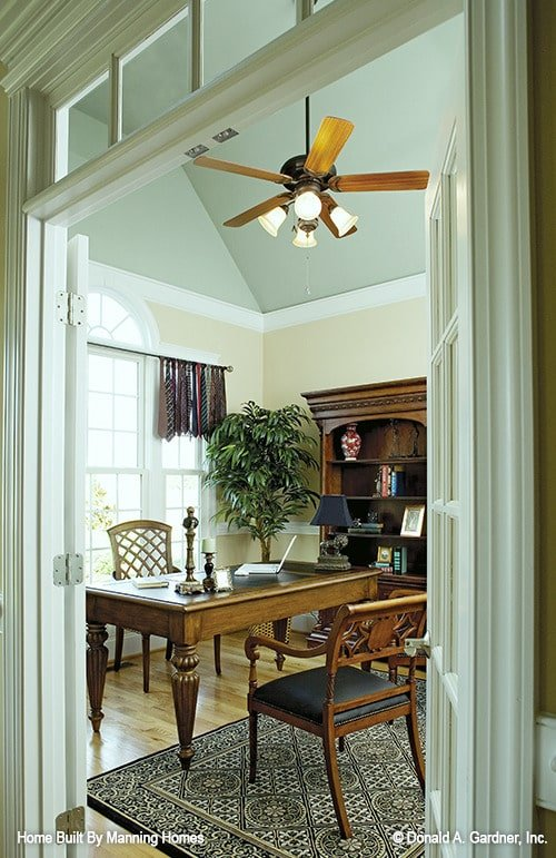 A french door opens to the study with dark wood furnishings and a large patterned rug that lays on the natural hardwood flooring.