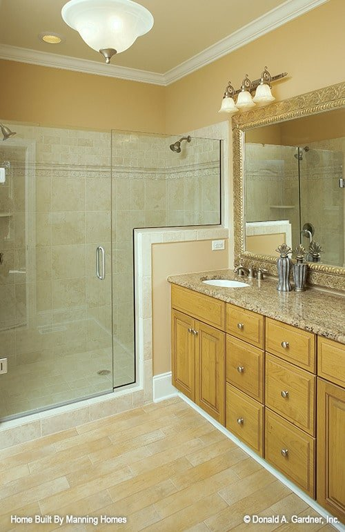 Primary bathroom with a walk-in shower and a sink vanity topped with a massive rectangular mirror.
