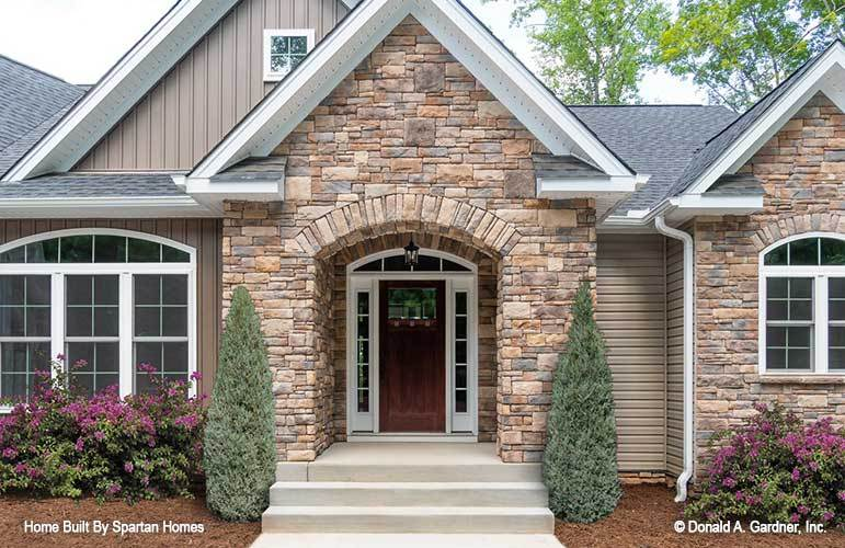 Home entry featuring an arched front door surrounded with glass panels.