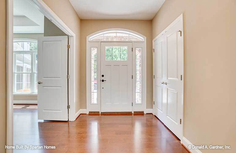 Foyer with a white entry door, polished hardwood flooring, and beige walls lined with white base molding.