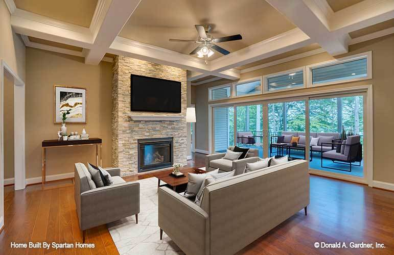 The living room offers a stone fireplace, wall-mounted TV, gray seats, and glass sliding doors that open out to the back porch.