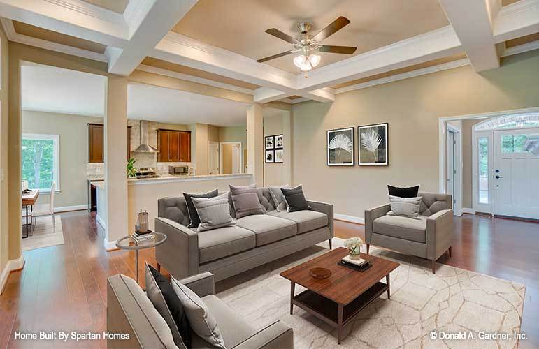 A coffered ceiling mounted with a fan crowns the living room