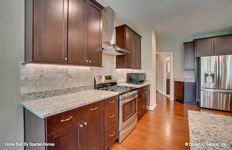 The kitchen is equipped with granite countertops, stainless steel appliances, wooden cabinetry, and subway tile backsplash.
