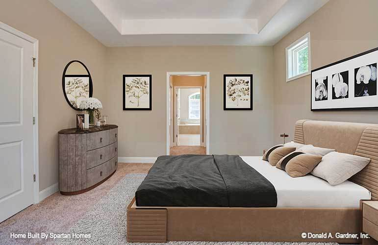 The primary bedroom has sleek furnishings, a tray ceiling, carpet flooring, and beige walls adorned with black-framed artworks and a round mirror.
