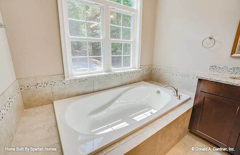 The deep soaking tub is placed under the white-framed windows bringing plenty of natural light in.