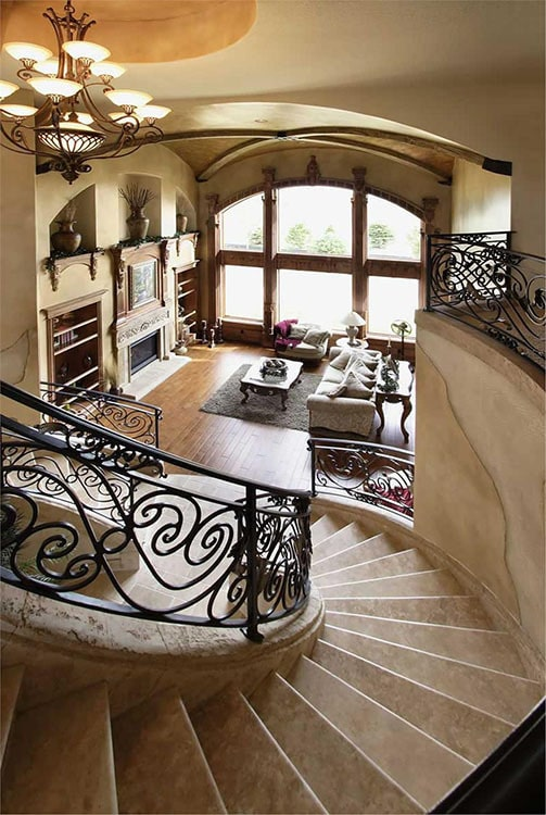 View of the living room from the elaborate winding staircase showing a massive arched window that brings plenty of natural light in.