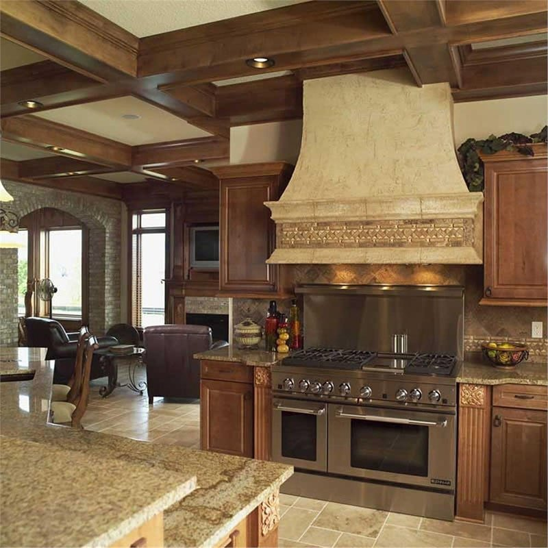 The kitchen offers a two-tier bar, wooden cabinets, and a double oven range placed under the bespoke vent hood.