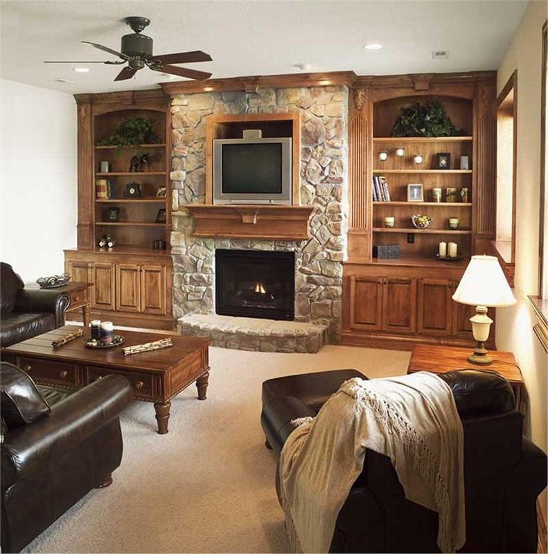 The family room has wooden tables, black leather seats, and a stone fireplace nestled in between the built-in shelves and base cabinets.