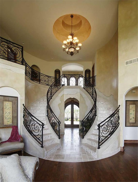 A magnificent bifurcated staircase illuminated by a warm ornate chandelier that hangs from the round step ceiling.