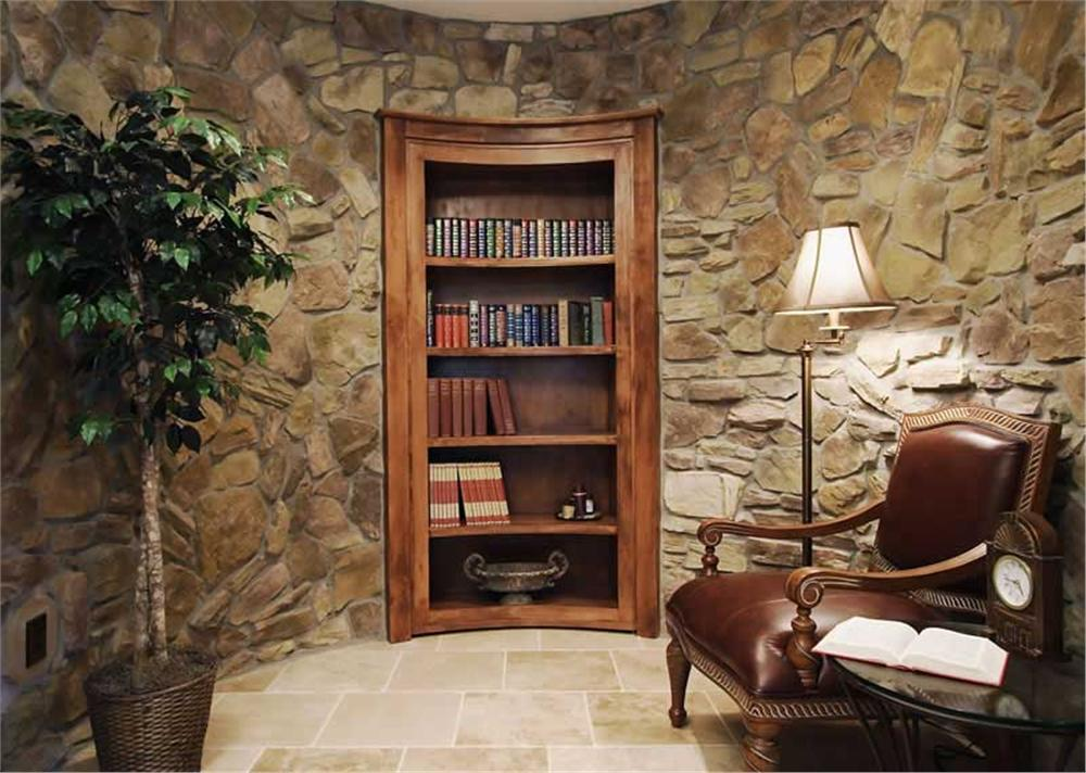 Quiet den with a round side table, a brown leather armchair, and an inset bookcase fitted on the curve stone wall.