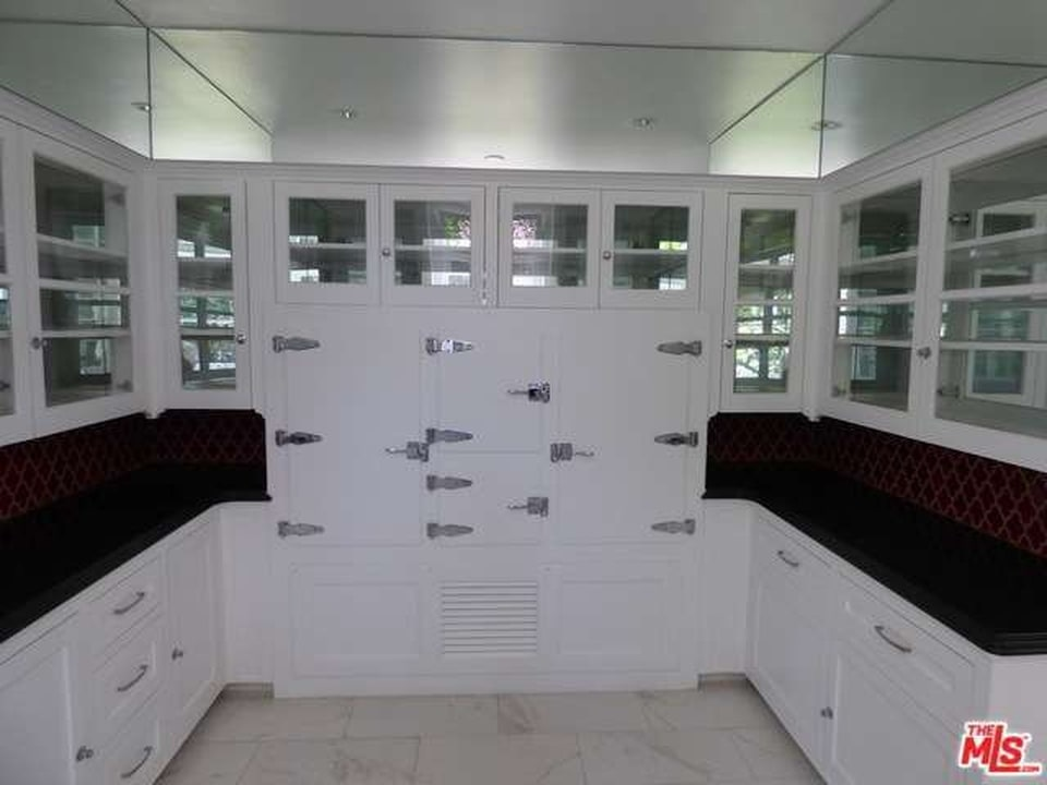 White kitchen with glass cabinets, red-patterned backsplash, and black countertops. Image courtesy of Toptenrealestatedeals.com.
