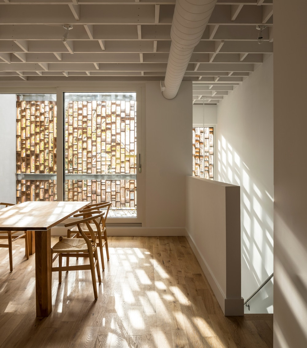 This is the dining room that has a simple wooden dining set that matches the hardwood flooring. You can also see here the wooden outer panel of the glass wall on the far side.