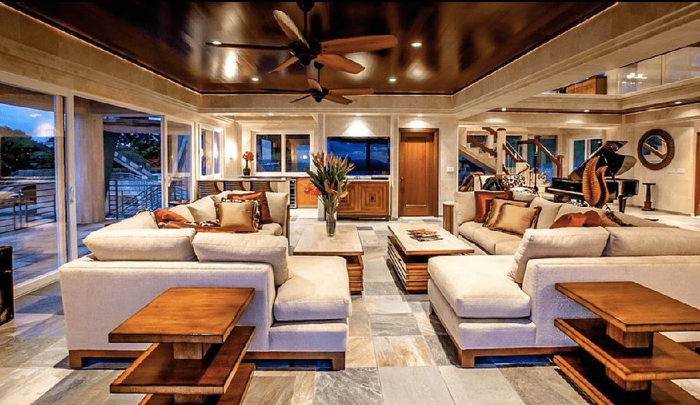 The living room features a tray ceiling with ceiling fans, white sectionals, wooden furniture, and glass sliding doors that lead to the stunning outdoor views. Image courtesy of Toptenrealestatedeals.com.
