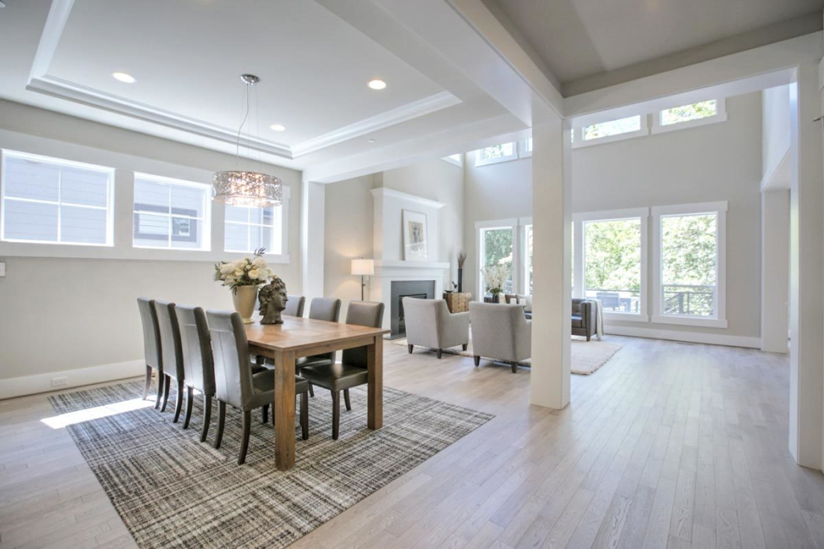 Shared dining and living room with gray walls and light hardwood flooring topped with large area rugs.