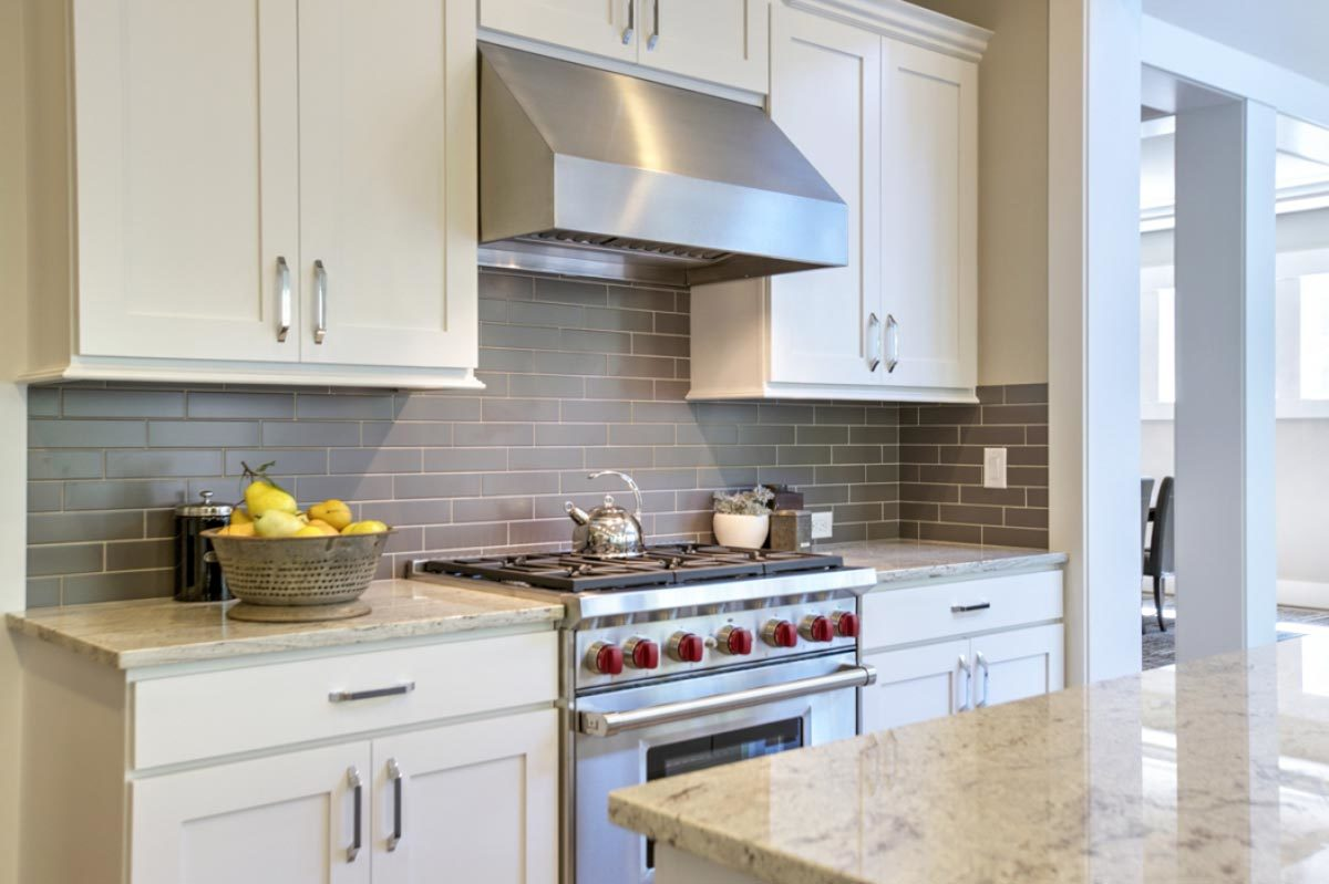 The stainless steel cooking range paired with a matching vent hood sits in between the white cabinets.