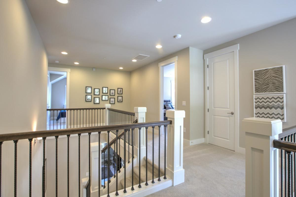 Second-floor balcony with carpet flooring and light gray walls adorned with photo gallery.