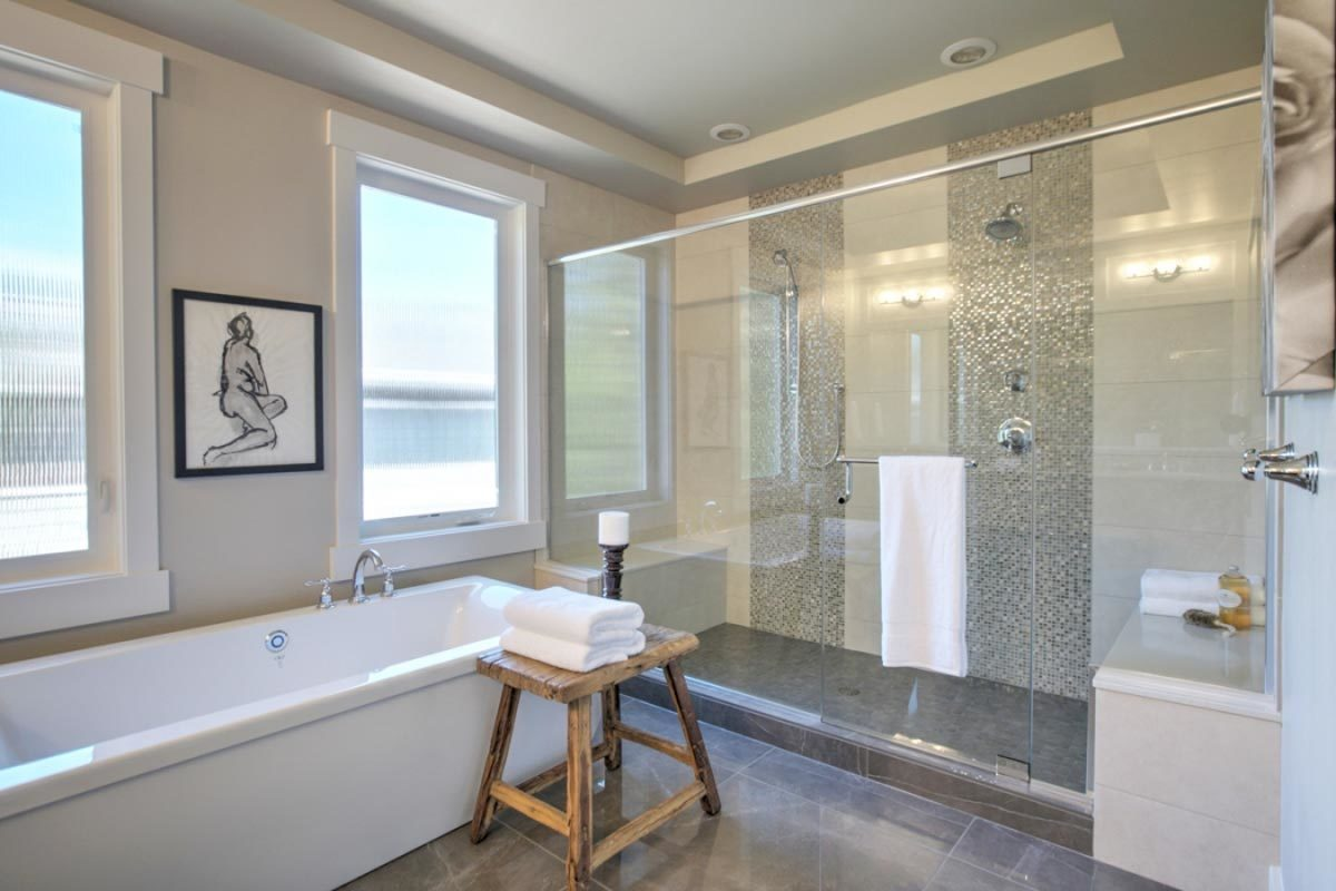Primary bathroom with a large walk-in closet and a freestanding tub complemented with a wooden stool.