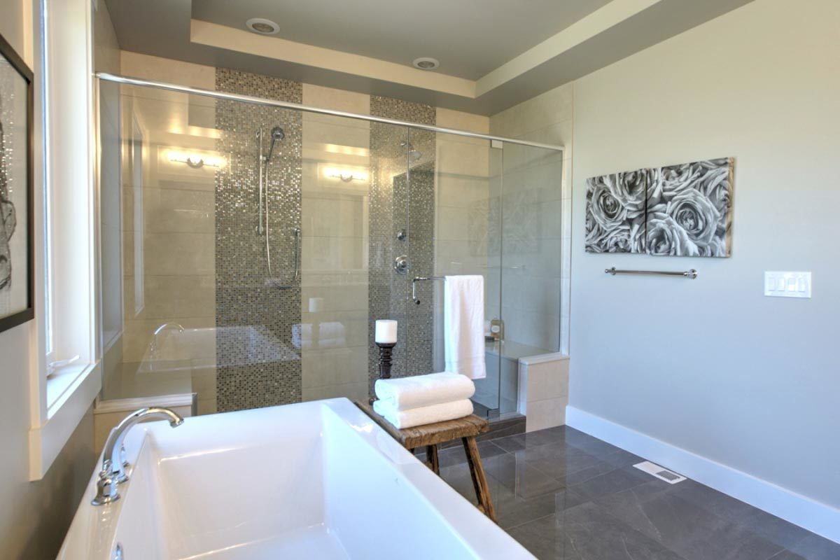 The walk-in shower offers a tiled bench and two shower heads accented with stunning mosaic tiles.