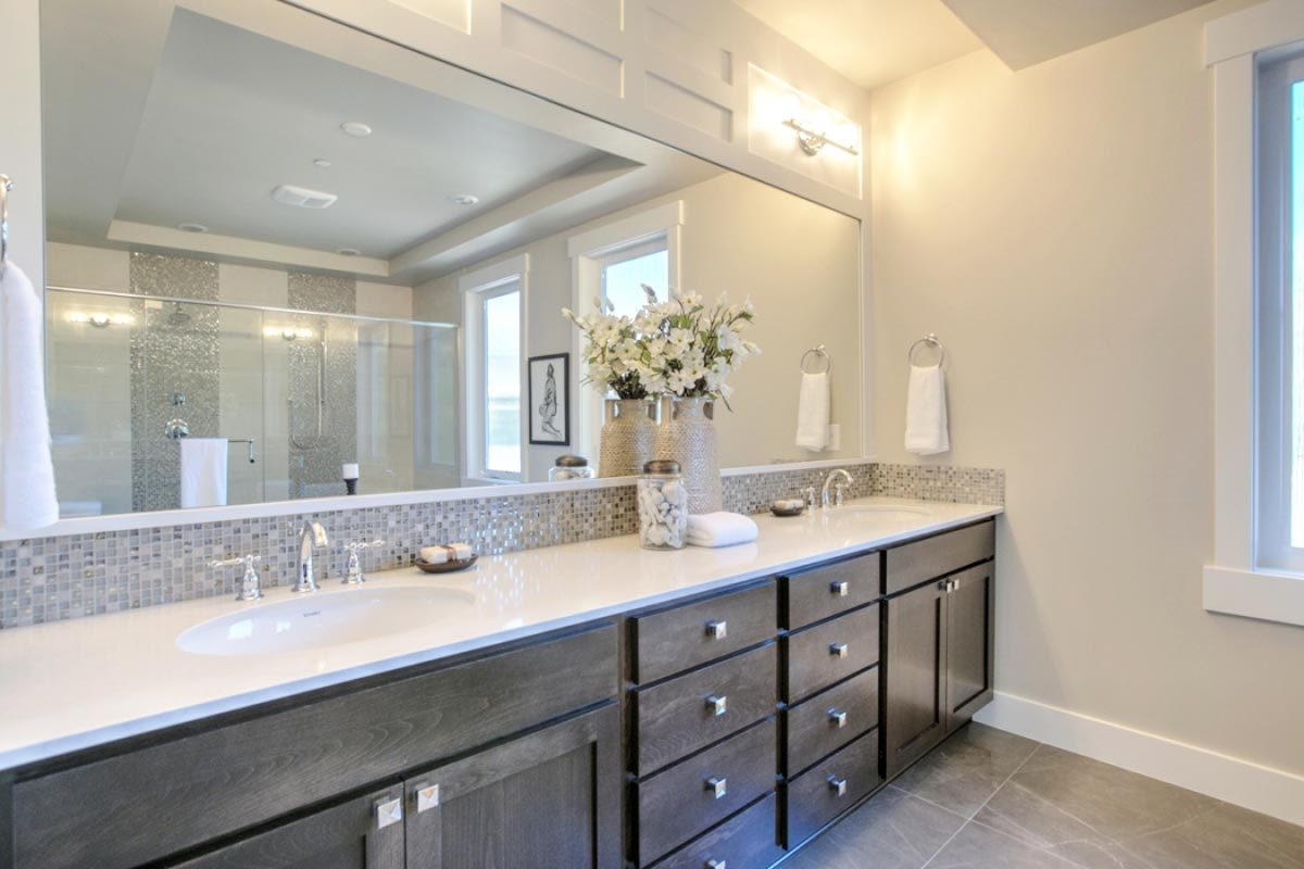 The dual sink vanity showcases dark wood cabinets, white granite countertop, and a frameless rectangular mirror.