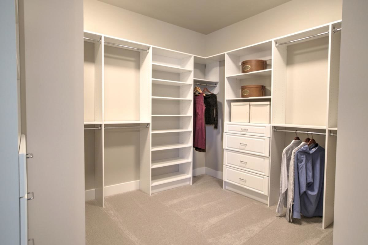 The walk-in closet is filled with white built-in shelvings and wardrobe poles.