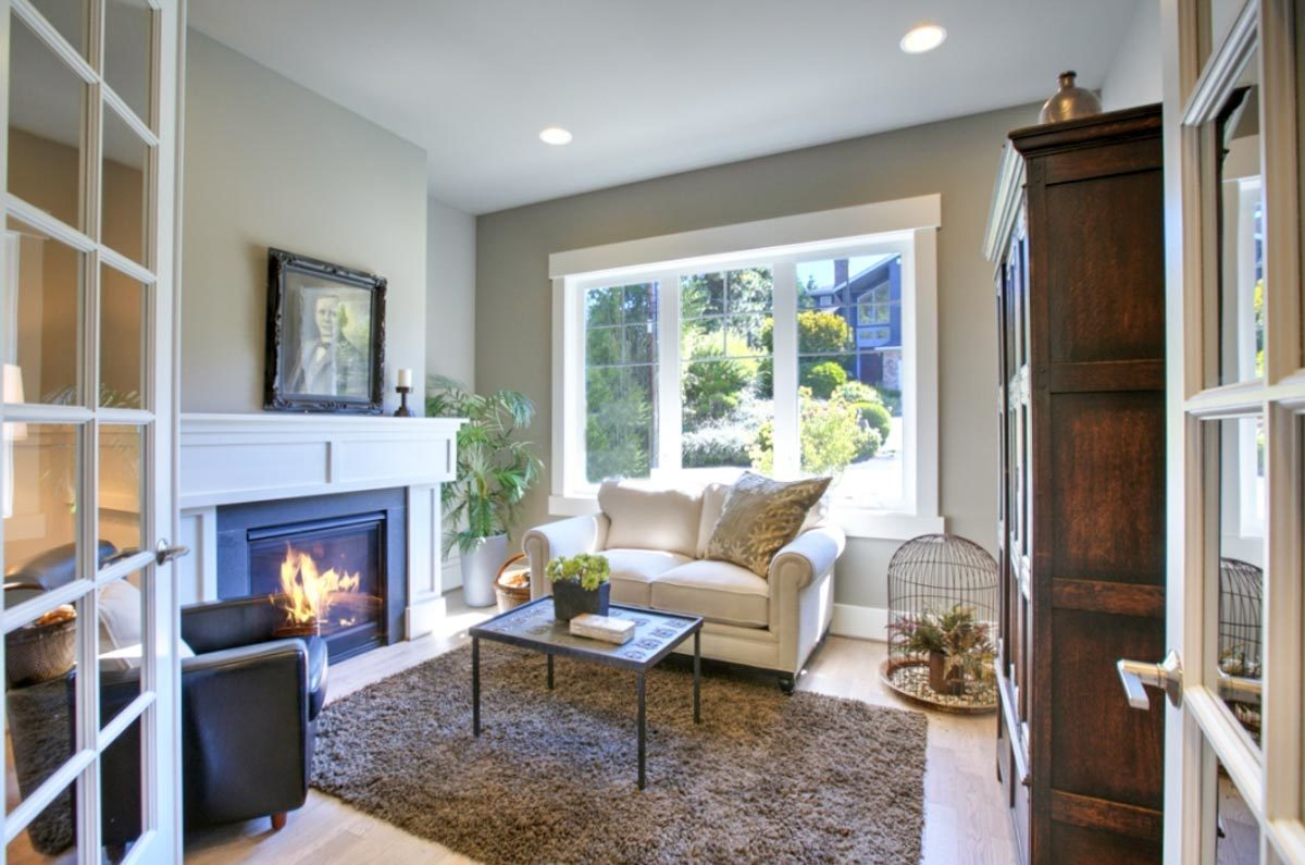 White french door opens to a quiet den with a fireplace and cozy contrasting seats paired with a metal coffee table.