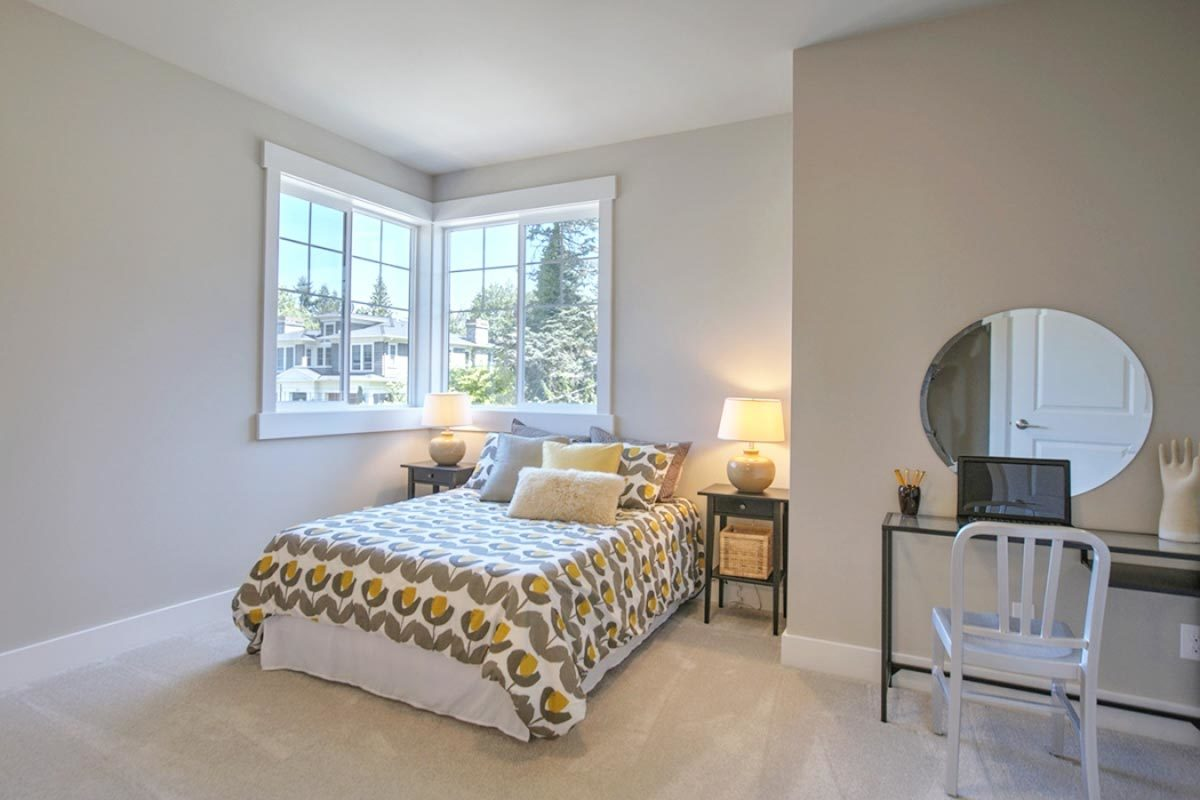 This bedroom offers a skirted bed and a metal desk complemented with a white chair and a round mirror.