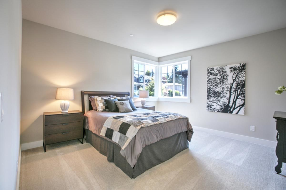 Another bedroom showcasing gray walls and carpet flooring along with white framed windows that invite natural light in.
