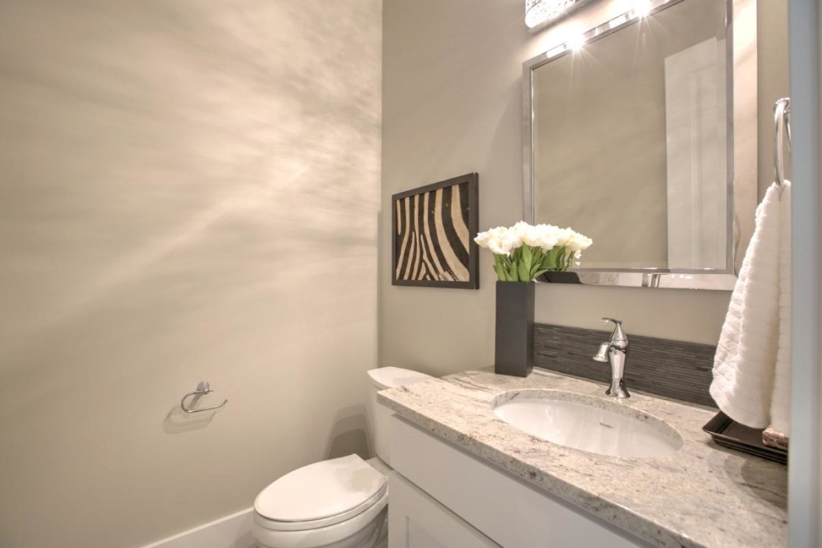 Bathroom with a toilet and a sink vanity crowned with a granite countertop.